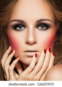 Beautiful model with black eye make-up, bright pink blusher and deep red manicure