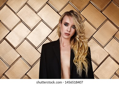 Beautiful Model in Black Jacket on Shiny Gold Background. Sexy Woman with Dark Fashion Makeup and Long Blond Hair.