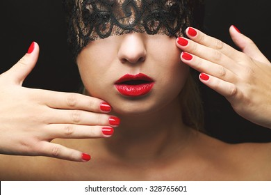 Beautiful model with black lace mask, red lips and manicure