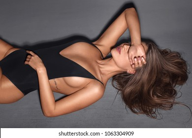 Beautiful model in a black one-piece swimsuit on a gray background