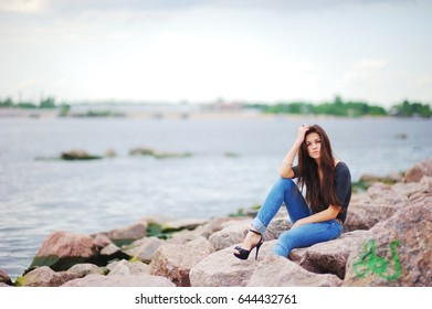 Beautiful model in a black t-shirt, stylish jeans and shoes on high heels posing while sitting on stones near water