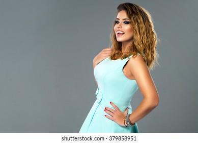 Beautiful model in blue dress posing in studio