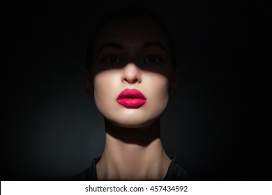 Beautiful model with bright pink lips and face half covered in shadow