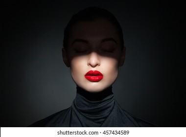 Beautiful model with bright red lips and face half covered in shadow