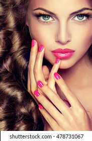 Beautiful model brunette with long curled hair . Hairstyle wavy curls . Crimson nails manicure .Makeup color fuchsia