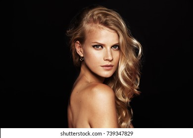beautiful model with curly blond hair on black background