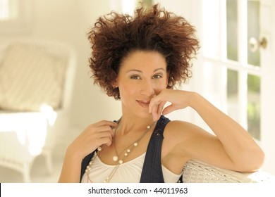 Beautiful model with curly hair in white room horizontal