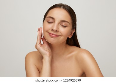 Beautiful model with eyes closed and naked shoulders posing at white studio background, close up, as standing near a mirror. Keeps palm near the face, stroking delicate healthy skin