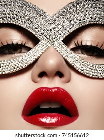 Beautiful Model with Fashion luxe Lips Make-up wearing bright brilliant mask. Masquerade style woman. Holiday celebration look