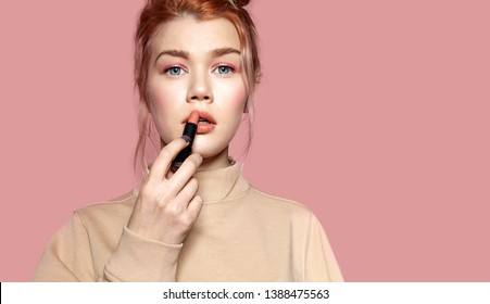 Beautiful model with full lips and blue eyes making stylish delicate visage. Portrait of perfect woman in casual sweater. Beauty and cosmetics concept. Isolated on pink