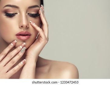 Beautiful model girl with a beige French manicure nail design with rhinestones . Fashion makeup and care for hands and nails and cosmetics .