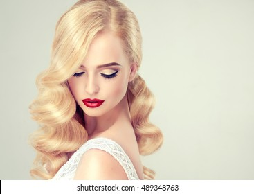 Beautiful model girl blonde  with long curled hair and  red lips . Hairstyle Hollywood wave