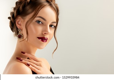 Beautiful model girl with burgundy or wine color manicure on nails . Fashion makeup and cosmetics . Jewelry, earrings and accessories. Beauty woman with braid hairstyle around her head.