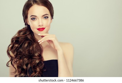 Beautiful    model  girl  with curly brown  hair . Brunette woman with wavy hairstyle  . Red  lips ,dress and  nails manicure .    Fashion , beauty and make up portrait