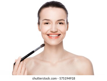 Beautiful model girl with cute smile holding makeup brush foundation on white background