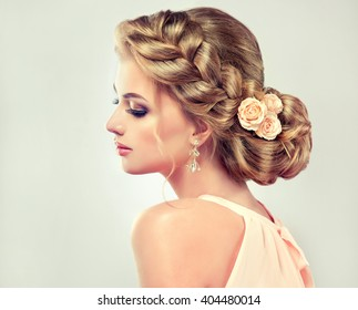 Beautiful model girl  with elegant hairstyle and rose flowers in a plait . Woman with fashion wedding hair.