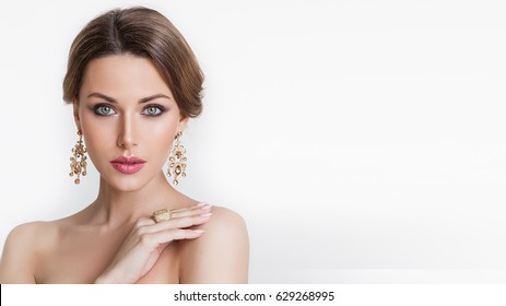 Beautiful model girl with elegant hairstyle . Woman with fashion wedding hair . Cosmetics, beauty and manicure on nails. Beauty woman  jewelry Golden long earrings and gold ring.