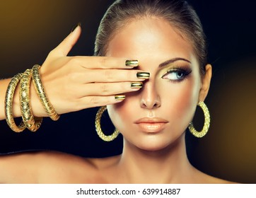Beautiful model girl with  Golden makeup and gold  metal manicure  nails.  Fashion woman Portrait . Jewelry, earrings and bracelets .