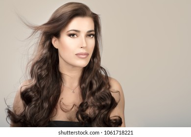 Beautiful model girl with healthy long wavy hair cascading over her shoulders over a beige studio background