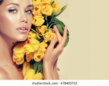 Beautiful model girl holding yellow tulips . Beautiful Young Woman with Clean Fresh Skin . Facial  treatment   . Cosmetology , beauty  and spa .