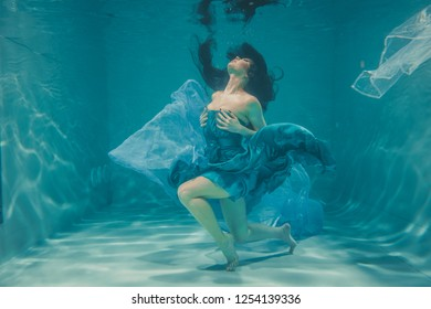 beautiful model girl with long black hair swims underwater in evening blue dress and enjoys relaxation and lack of stress