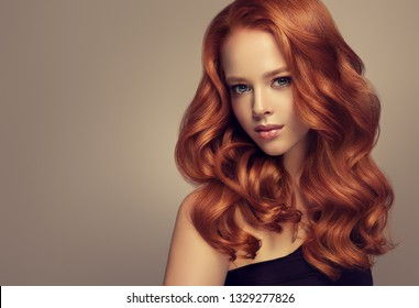 Beautiful model girl with long curly red hair . Styling hairstyle curls .Wavy and shiny swirl .