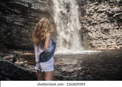 Beautiful model girl with long legs posing near a waterfall wearing jeans jacket