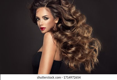 Beautiful model girl with long wavy and shiny hair . Brunette woman with curly hairstyle and red lips