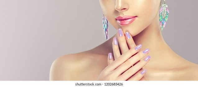 Beautiful model girl with pearl  color manicure on nails . Fashion makeup  and cosmetics . Big multicolored  turquoise shades  earrings jewelry .