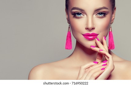 Beautiful model girl with pink fuchsia manicure on nails . Fashion makeup and cosmetics . Large earrings tassels jewelry Magenta color . - Shutterstock ID 716950222
