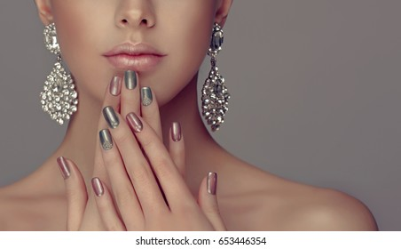 Beautiful model girl with pink and gray  silver  metallic manicure on nails . Fashion makeup and cosmetics . Big silver diamond shine  earrings jewelry .