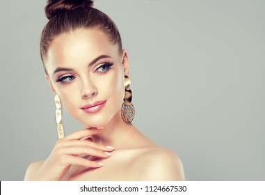 Beautiful model girl with pink manicure on nails . Fashion makeup and cosmetics . Big golden shine  earrings jewelry .