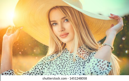 Beautiful model girl posing on a field, enjoying nature outdoors in wide brimmed straw hat. Beauty blonde young woman with long straight blond hair close-up portrait