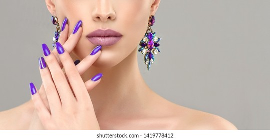 Beautiful model girl with purple or  violet manicure on nails . Fashion makeup and cosmetics . Large earrings  jewelry .