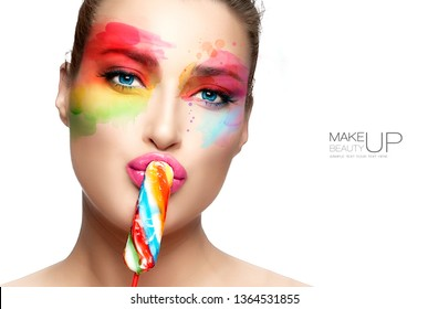 Beautiful model girl with rainbow colored artistic eye makeup kissing a spiral rainbow lollipop with sensual pink lips. Fine art beauty portrait isolated on white. Fashion makeup and cosmetics concept