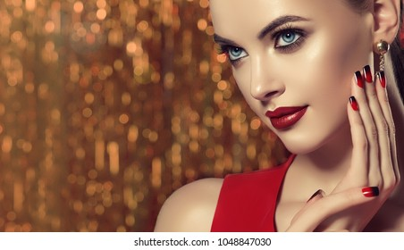 Beautiful model girl with red and black  french manicure on nails . Fashion luxury makeup . Dark red lips and shiny eye shadow pigment . Beauty  and cosmetics . Golden brilliant   background .