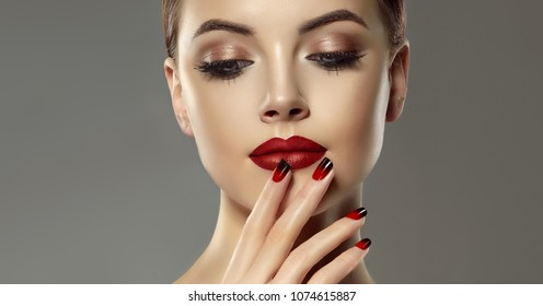 Beautiful model girl with red and black  french manicure on nails . Fashion luxury makeup . Cherry color lips and shiny eye shadow pigment . Beauty  and cosmetics .