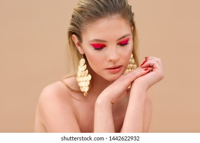 Beautiful model girl with red manicure on nails. Fashion bright make up and cosmetics. Wearing big golden shine earrings jewelry