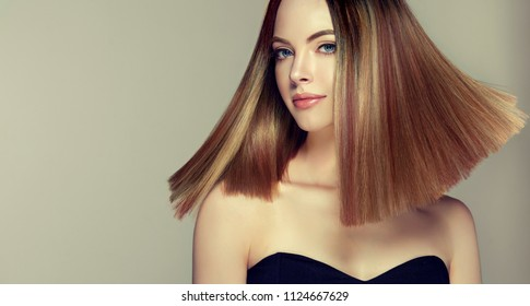 Beautiful model girl with shiny brown and straight long  hair . Keratin  straightening . Treatment, care and spa procedures. Medium length hairstyle. Coloring, ombre, shatush, balage and highlighting