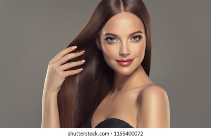 Beautiful model girl with shiny brown and straight long  hair . Keratin  straightening . Treatment, care and spa procedures. Smooth hairstyle. Care and beauty  products .