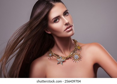 Beautiful model girl with shiny brown straight long hair. Care and hair products.