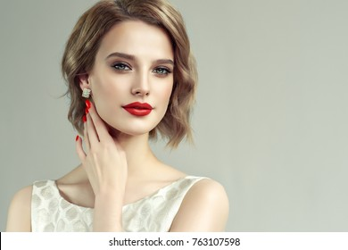 Beautiful model girl with short curly  hair and red lips . Red manicure on nails .Beauty and esthetic care