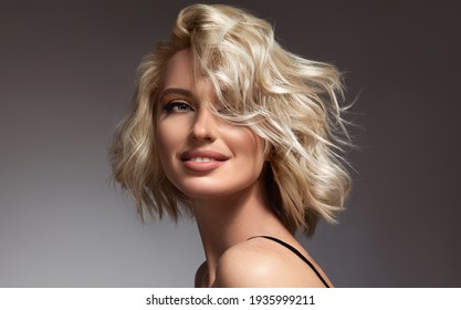 Beautiful model girl with short hair .Beauty  smiling woman with blonde curly hairstyle dye .Fashion, cosmetics and makeup