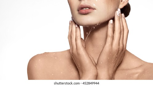 Beautiful Model Girl with splashes of water in her hands. Beautiful Smiling Woman under splash of water with fresh skin over white background. Skin care Cleansing and moisturizing concept. Beauty face