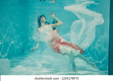 beautiful model girl swimming underwater in feminine long white and pink dress