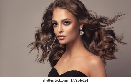 Beautiful model girl with wavy and shiny hair . Brunette woman with curly hairstyle,earrings and jewelry