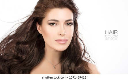 Beautiful model girl wearing subtle makeup with long wavy healthy brown hair isolated on white in a cropped view conceptual of hair care and hair styling products