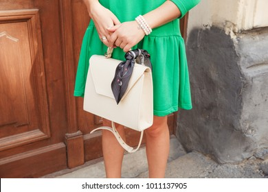 Beautiful model in grass green cotton dress walking on the city streets with milky lether purse in hand. Woman in dress with leather handbag, street fashion look, summer outfit