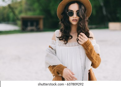 Beautiful model in hat and dress in hippie style posing on summer beach