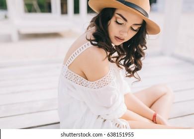 Modelo bonito em chapéu e vestido em estilo hippie posando na praia de verão